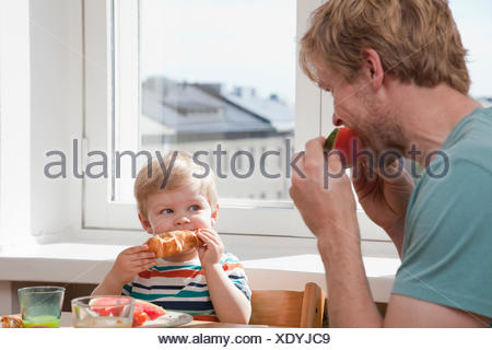 Father and toddler son eating breakfast at kitchen table - Stock Photo