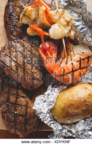 Surf and Turf beef steaks and prawns with baked potato FoodCollection - Stock Photo