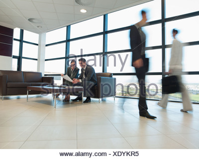 Business people working together in office waiting area - Stock Photo