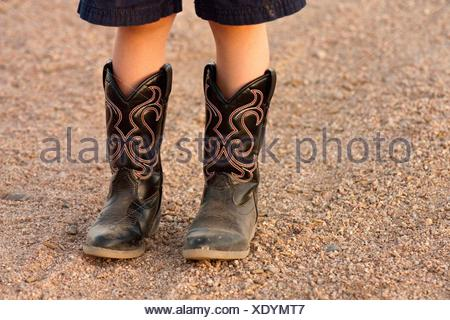 A kids boots, standing on the gravel - Stock Photo
