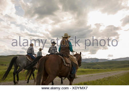 Female ranchers horseback riding on remote road - Stock Photo