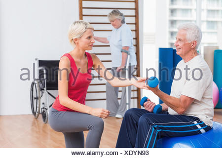 Trainer assisting senior man in exercising with dumbbells - Stock Photo
