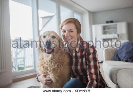 Portrait of smiling young woman   her dog at home - Stock Photo