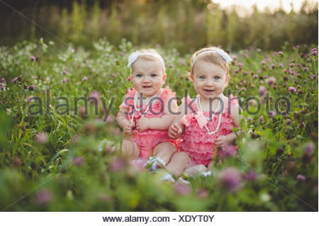 Portrait of baby twin sisters sitting in wild flower meadow wearing pink party dresses - Stock Photo