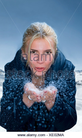 Young woman blows snow from hands - Stock Photo