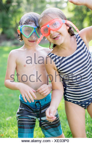 Portrait of boy and girl in garden wearing swimming goggles - Stock Photo