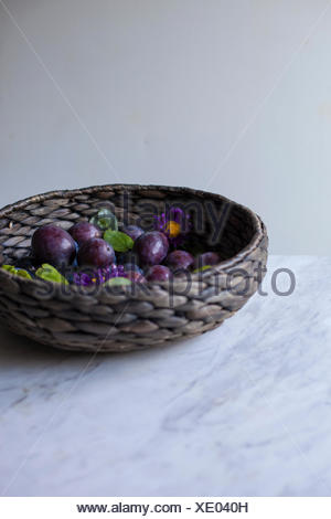 Fresh plums in a large basket on a white marble table - Stock Photo