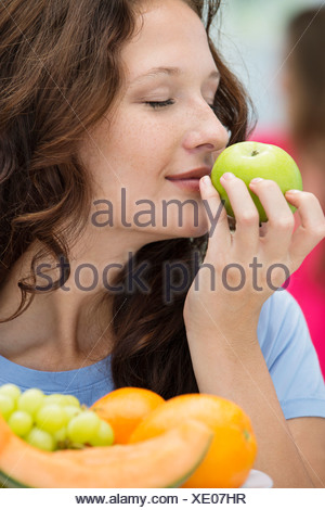Close-up of a woman smelling a green apple - Stock Photo