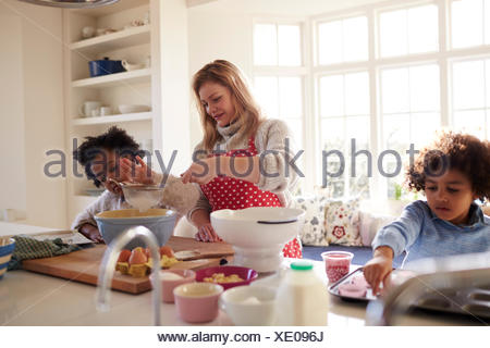 Mother Baking Cake With Children In Kitchen At Home - Stock Photo