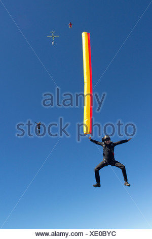 Woman skydiving with parachute - Stock Photo