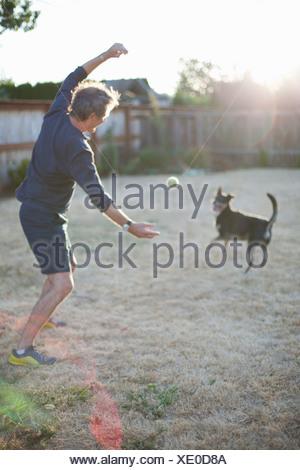 Senior Caucasian man plays with a dog - Stock Photo