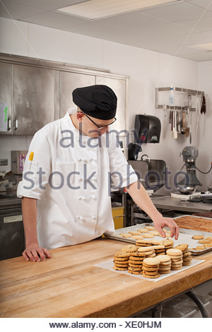 Male chef baking cookies in commercial kitchen - Stock Photo