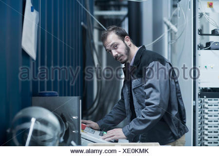 Young male engineer updating control panel in control room, Freiburg Im Breisgau, Baden-Württemberg, Germany - Stock Photo