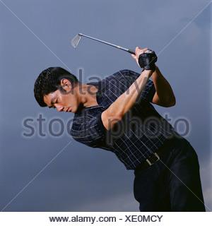 Man swinging golf club - Stock Photo