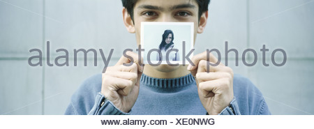 Young man holding up photo of young woman - Stock Photo
