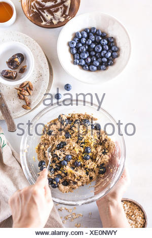 Blueberries are being mixed into the dough for breakfast scones. - Stock Photo