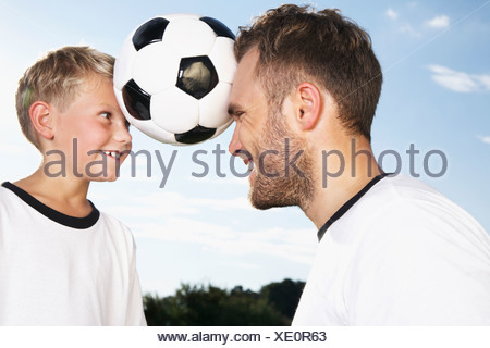 Germany, Cologne, Father and son playing soccer - Stock Photo