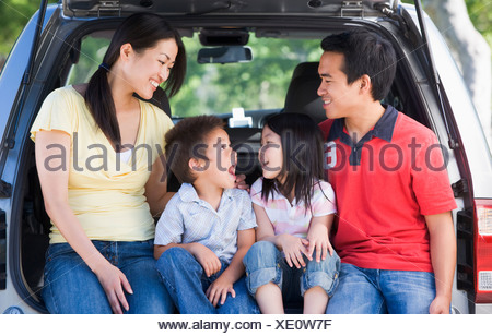 Family sitting in back of van smiling - Stock Photo