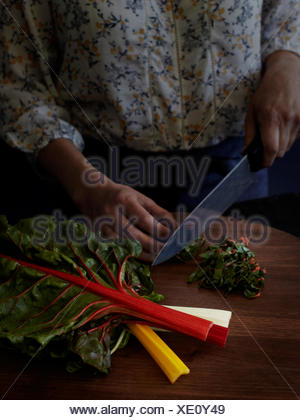 Cropped view of woman chopping rainbow chard with kitchen knife - Stock Photo