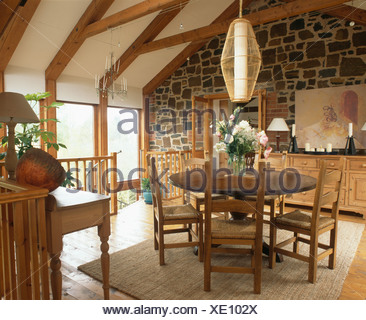 Cylindrical light above circular mahogany dining table and rush-seated chairs in upstairs dining room with exposed stone wall - Stock Photo