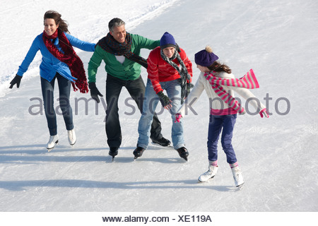 Family ice-skating on frozen lake together - Stock Photo