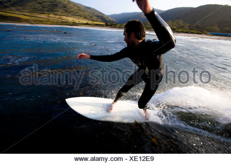 A male surfer does a turn while riding a wave at Leo Carrillo State Park in Malibu, California. - Stock Photo