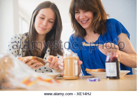Mother and daughter (14-15) making peanut butter and jelly sandwiches - Stock Photo