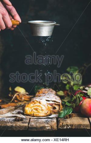 Apple strudel cake cut in pieces with fresh red apples on rustic wooden table and man's hands with sieve sprinkling sugar powder - Stock Photo