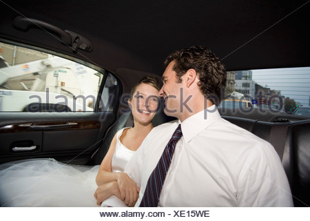 A bride and groom in a car - Stock Photo