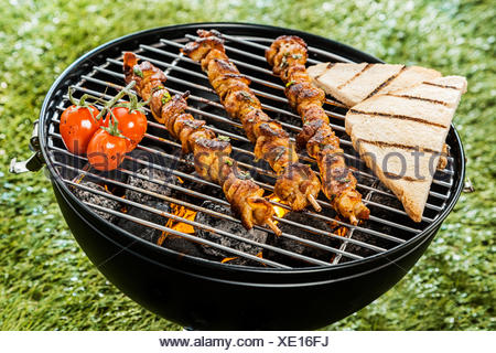Three delicious meat kebabs grilling on a BBQ fire with slices of toast and tomatoes during a summer picnic in the garden, close up high angle view - Stock Photo
