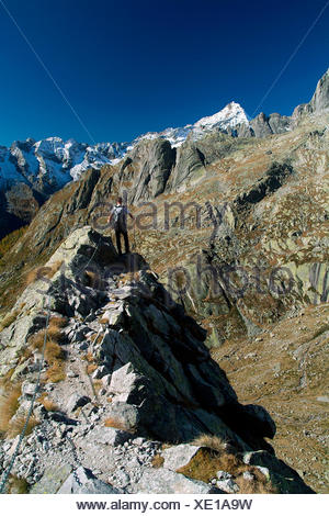 Hiker overlooking towards the Mount Disgrazia by a walking section of the trail Rome. Valmasino. Valtellina. Lombardy Italy Europe - Stock Photo