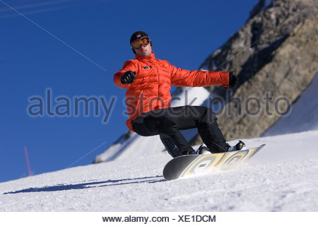 Snowboarder with arms out balancing on mountainside, Tignes, France - Stock Photo