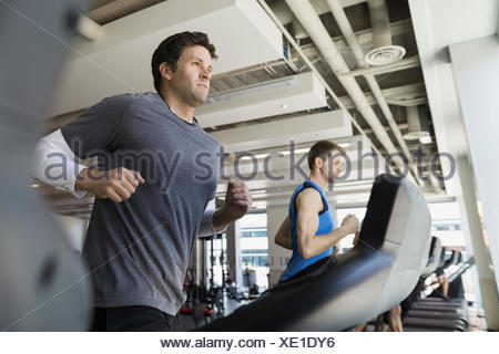Determined man jogging on treadmill at gym - Stock Photo