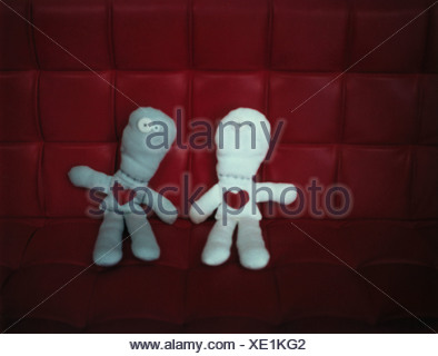 Two rag dolls side by side on red sofa, front view - Stock Photo