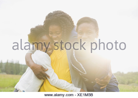 Cheerful mother and daughters hugging outside - Stock Photo