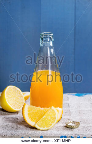 Opened glass bottle of citrus orange and lemon lemonade, standing with sliced fruits on stone board with blue background. With c - Stock Photo