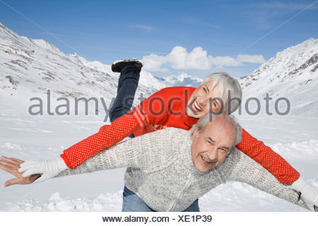 Portrait of happy senior couple in mountains on winter day - Stock Photo