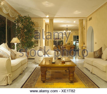 white sofa cover with wooden table | Large white sofas in yellow Spanish living room with ...
