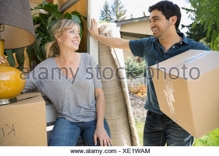 Couple unloading belongings from moving van - Stock Photo