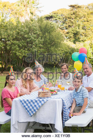 Happy family smiling at camera at birthday party - Stock Photo
