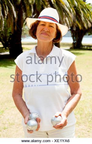 Portrait of senior woman with boule balls in park - Stock Photo