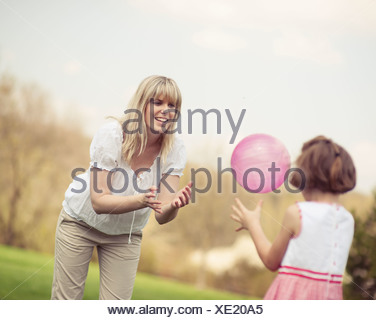 Family throwing ball to each other in the park - Stock Photo