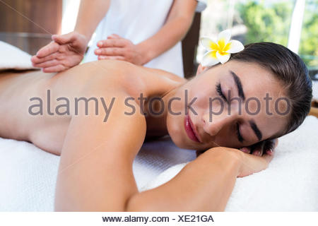 Masseuse giving massage to relax woman - Stock Photo