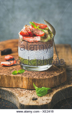 Healthy vegan breakfast concept. Matcha, almond milk, cocoa chia seed pudding with fresh fruit, berries, mint, chocolate in glass over wooden board, g - Stock Photo