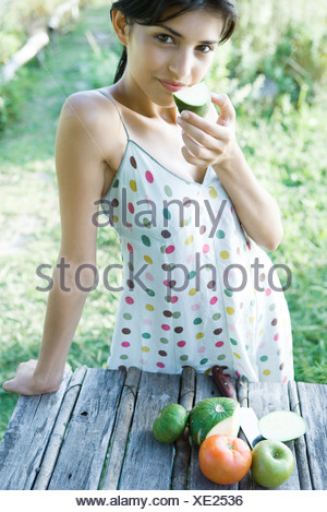 Young woman standing near pile of fresh produce, holding up slice of fruit to mouth, smiling at camera - Stock Photo