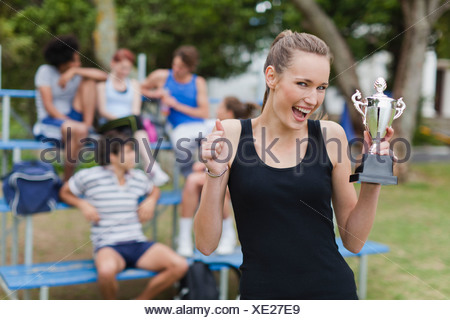Woman holding trophy in park - Stock Photo