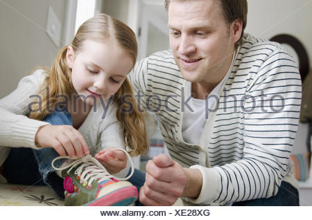 dad helping young daughter tie shoe laces - Stock Photo