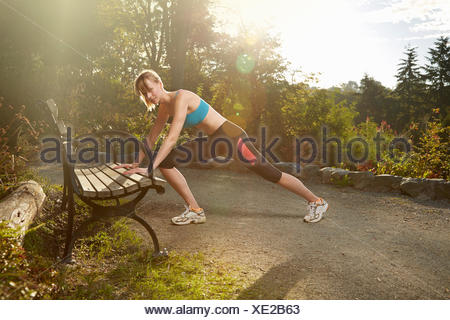 Mid adult woman runner stretching against park bench - Stock Photo