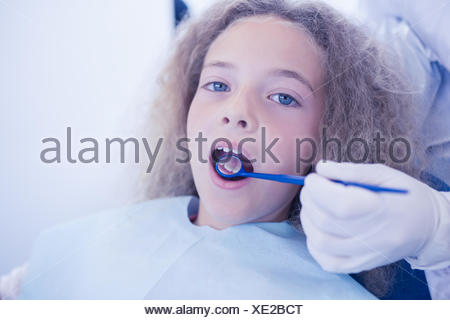 Dentist examining a patients teeth in the dentists chair - Stock Photo