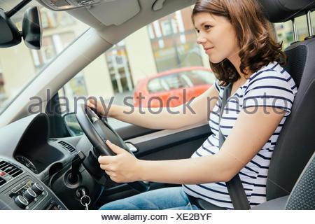 Pregnant woman driving car - Stock Photo